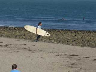 Malibu surfer on Zuma Beach near sunset